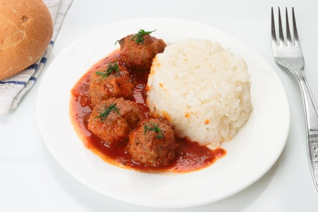 Hot meatballs with rice in tomato sauce served on table