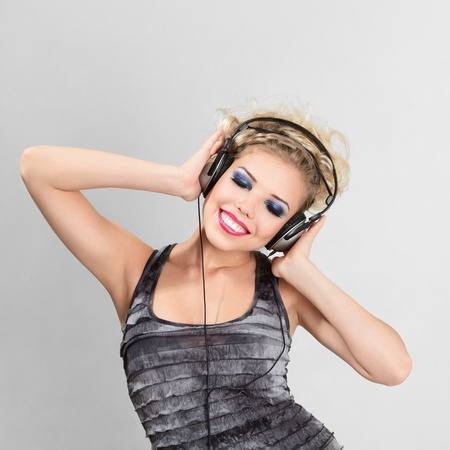 Young blonde woman with headphone listening to music photo