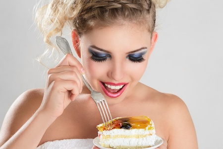 Beautiful blonde woman eating a cake slice on plate photo