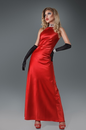 Beautiful blond girl in long elegant red dress against dark gray background photo