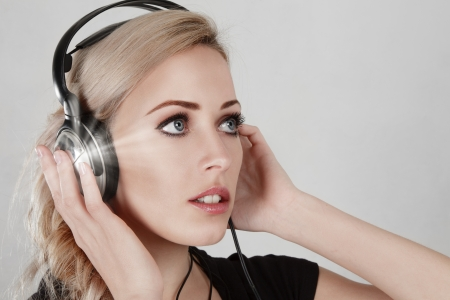Young blonde woman with headphone listening music Stock Photo - 15638817