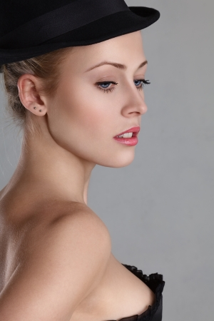 Beautiful blonde young woman with blue eyes in fashion hat profile portrait