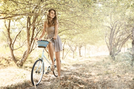 active holiday: Young woman with retro bicycle in a park - outdoor portrait