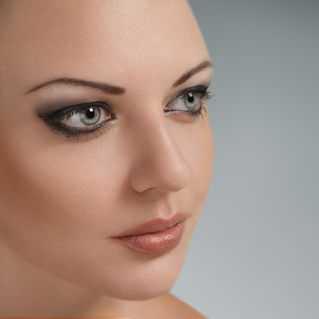 sidewards: Attractive young woman close-up portrait with perfect skin looking away