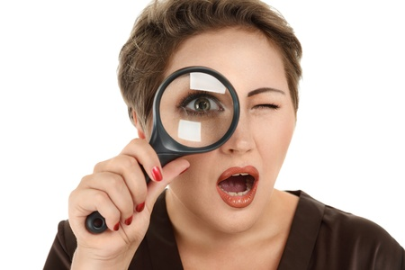 Beautiful woman looking through a magnifying glass photo