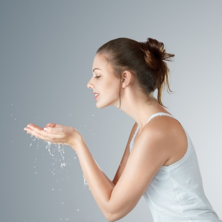 Young woman washing his face and hands with clean water in the morning photo