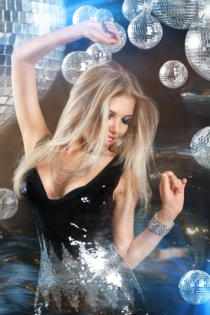 Young blonde woman dancing at night disco club