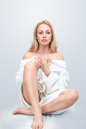 white robe: Beautiful blond woman sitting on floor in bathrobe