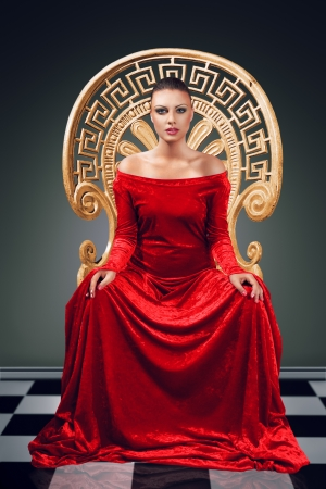 A woman in a luxurious red dress sitting on a golden throne