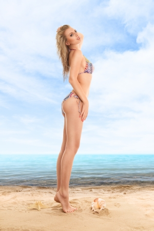 Beautiful young woman in a swimsuit posing against water at beach photo