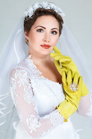 Bride posing with yellow rubber household gloves photo