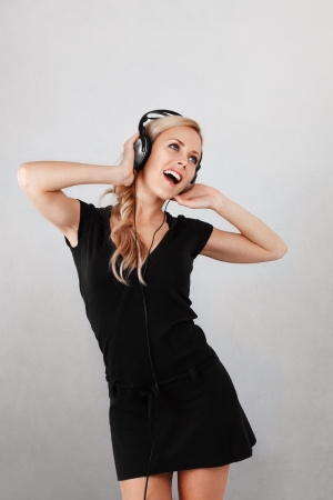 Young blonde woman listening music in headphones Stock Photo - 17591781