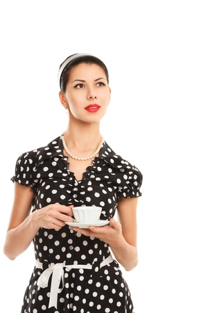 polka dot: Young woman in vintage polka dot dress with tea posing against white background