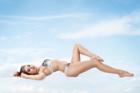 Young sexy woman in lingerie relaxing on soft cloud against blue sky photo