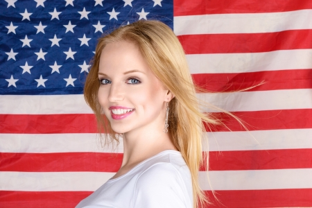 see the usa: Young beautiful happy blonde woman posing against american flag at background
