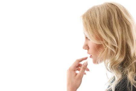 sidewards: Young blonde woman touching lips close-up portrait isolated on white background Stock Photo