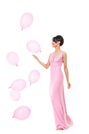 Young happy barefoot woman in long pink dress goes tiptoe isolated over white background photo
