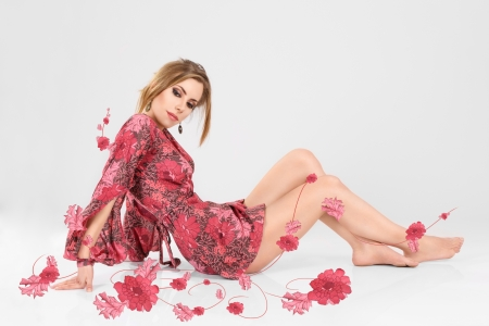 Young beautiful woman in short pink mini dress made from flowers sitting on floor photo