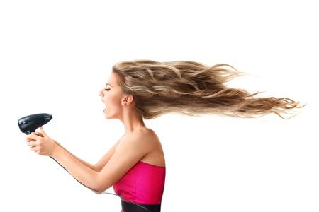 secador de pelo: Mujer joven rubia secar el cabello largo con ventilador eléctrico aislado en el fondo blanco Foto de archivo
