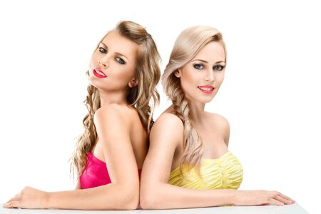 seductive women: Portrait of two young beautiful blonde women isolated on white background