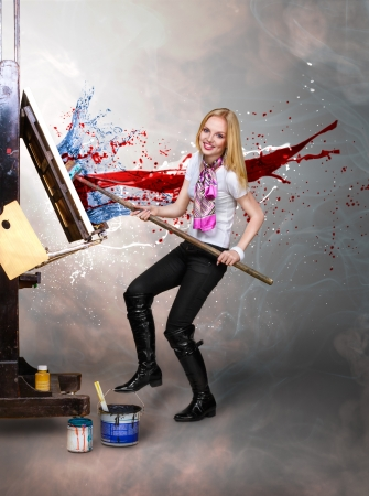 Young creative painter artist blonde woman paint on canvas with big paintbrush Stock Photo