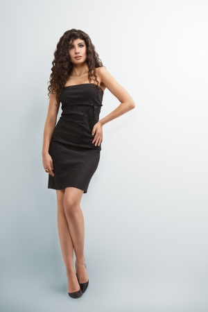 Elegant woman in little black dress with long curly hair photo