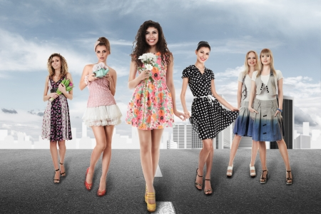 alluring women: Large group of young women walking on road against abstract city Stock Photo