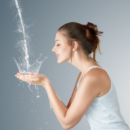 mujer ba�andose: Mujer joven lavando la cara y las manos con agua limpia por la ma�ana