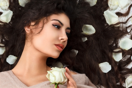 Attractive young woman with flower petals over long curly hair lying down photo
