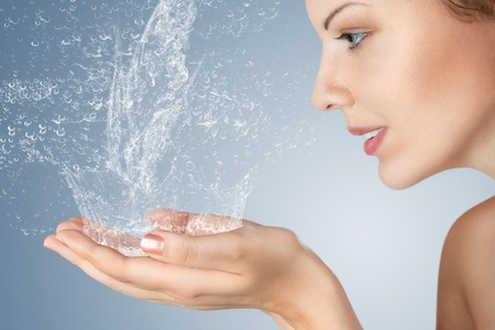 Young woman washing her face and hands with clean water in the morning photo