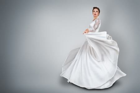 evening dress: Happy young bride in beautiful long wedding dress Stock Photo