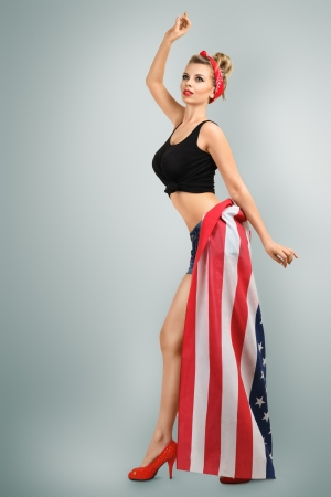 Young blonde woman in skirt from flag pin-up style studio portrait photo