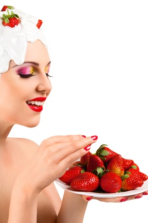 Young woman with hairstyle made from milk eating red ripe strawberry photo