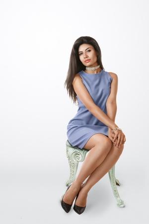minifalda: Mujer elegante joven en mini vestido azul que se sienta en la silla de estudio de retrato Foto de archivo