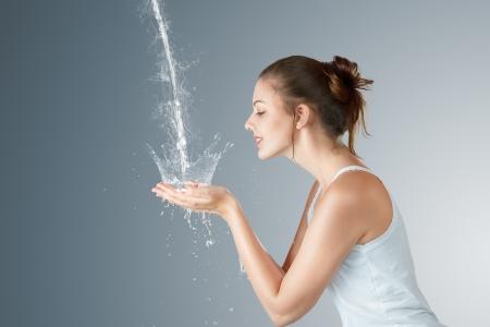perfil de mujer rostro: Mujer joven lavando la cara y las manos con agua limpia por la ma?ana Foto de archivo