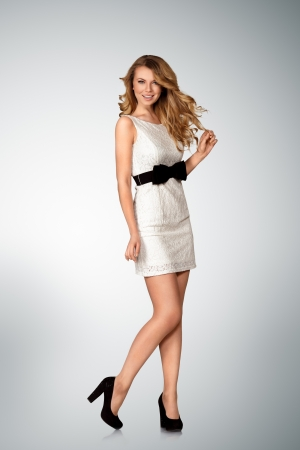 Young woman posing in white mini dress full length portrait