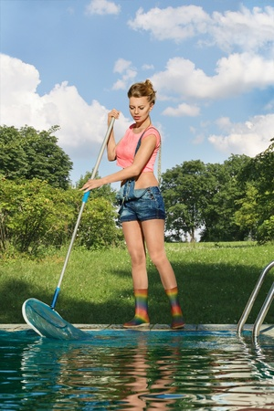 Young woman cleaning swimming pool photo