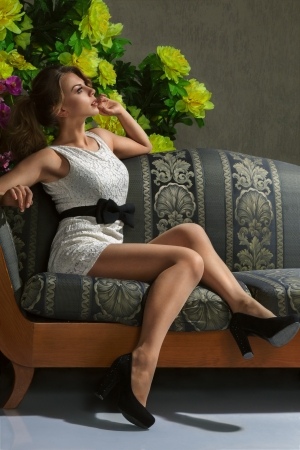 Young beautiful luxurious woman sitting on a vintage couch photo