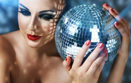 Close-up face of young woman with fashionable make-up and disco ball in hands Archivio Fotografico