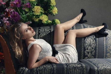 Young beautiful luxurious woman lying on a vintage couch photo