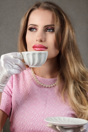 sidewards: Young blonde woman with cup of tea looking sidewards retro style portrait