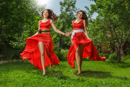 Two young happy beautiful fashion women in long red dress running on green grass photo