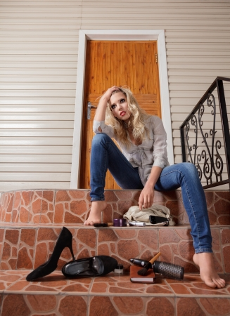 Young sad woman lost her house keys. Girl sits in front of the door Stock Photo