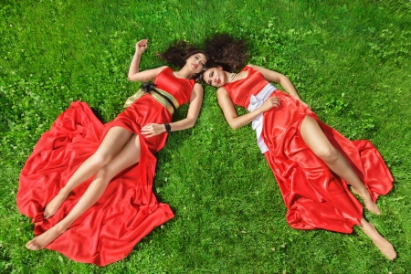 lying on grass: Two young women in a luxurious red dresses lie on the grass Stock Photo