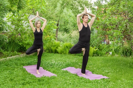 tree position: Young man and woman doing youga. Tree pose meditation in a garden. Outdoor full body.