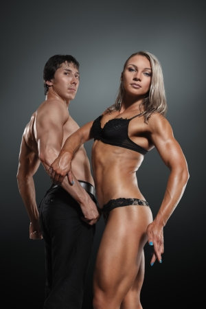 Athletic young woman and man posing together against dark studio background photo
