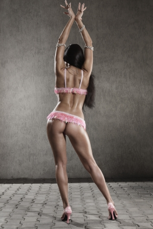 Young woman in stage costume of Go-go dancer posing on studio. rear view photo