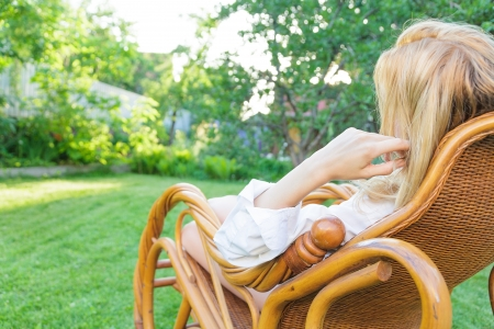 Young blonde woman relax at outdoor sitting in a rocking chair
