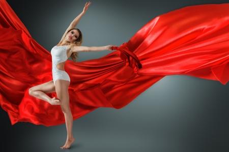 Woman in white swimwear dancing with flying fabric Reklamní fotografie