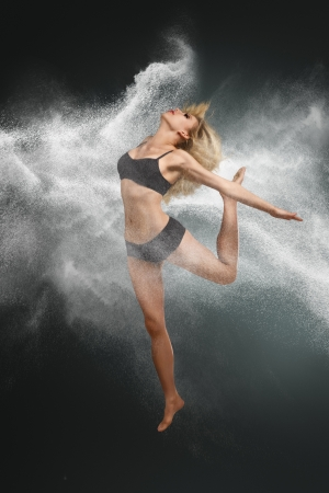 Young beautiful dancer jumping into white powder cloud against dark background photo